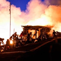 Los residentes de Kibera forman una cadena humana mientras pasan agua para extinguir un incendio que destruyó a los chabolas en el área de Maranatha del extenso barrio pobre que comenzó al anochecer en Nairobi.   Foto:Gordwin Odhiambo / AFP