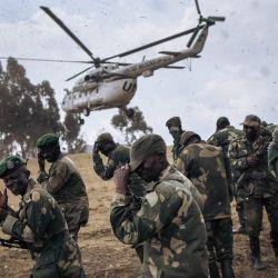 Los soldados del ejército congoleño protegen sus rostros de las proyecciones cuando un helicóptero de la Misión de Estabilización de la Organización de las Naciones Unidas en la República Democrática del Congo aterriza en Bijombo, provincia de Kivu del Sur, en el este de la República Democrática del Congo. | Foto:Alexis Huguet / AFP