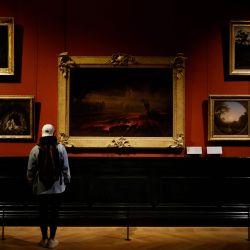 Un visitante observa pinturas británicas en el Museo del Louvre, abandonado por los turistas debido a la pandemia de Covid-19, en París. | Foto:Ludovic Marin / AFP