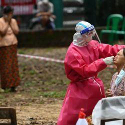 Un trabajador médico toma una muestra de hisopo de una mujer para realizar la prueba del coronavirus COVID-19 en una instalación de cuarentena en Yangon. | Foto:Ye Aung Thu / AFP