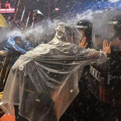 Los manifestantes a favor de la democracia rechazan a la policía antidisturbios mientras disparan cañones de agua durante una manifestación antigubernamental en Bangkok. | Foto:Lillian Suwanrumpha / AFP