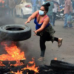 Un vendedor ambulante arroja una llanta a una barricada en llamas durante una protesta para exigir al gobierno del presidente hondureño Juan Orlando Hernández que les permita trabajar en el mercado de Belén en medio de la crisis económica desencadenada por la nueva pandemia de coronavirus, en Tegucigalpa.   Foto:Orlando Sierra / AFP