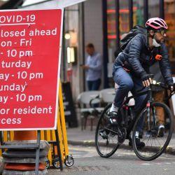 Un ciclista pedalea más allá de una señal de tráfico que muestra los tiempos de los cierres de carreteras debido a COVID-19, en Soho en el West End de Londres, ya que nuevas restricciones a las reuniones sociales y el movimiento entrarán en vigor en Londres para Combatir la propagación del nuevo coronavirus COVID-19.   Foto:Ben Stansall / AFP