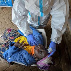 Una anciana reacciona a un hisopo nasal durante una prueba masiva para el coronavirus COVID-19 proporcionada de forma gratuita por el gobierno de Kenia en el barrio pobre de Kibera en Nairobi.   Foto:Tony Karumba / AFP