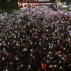 Los manifestantes a favor de la democracia sostienen linternas en los teléfonos durante una manifestación en Bangkok, luego de que Tailandia emitiera un decreto de emergencia luego de una manifestación antigubernamental el día anterior.   Foto:Jack Taylor / AFP