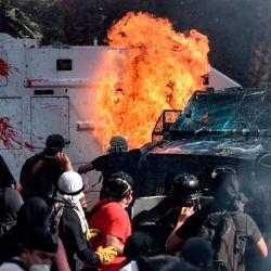 Los manifestantes prendieron fuego a un vehículo de la policía antidisturbios durante los enfrentamientos en la conmemoración del primer aniversario del levantamiento social en Chile, en Santiago, mientras el país se prepara para un referéndum histórico. | Foto:Martin Bernetti / AFP