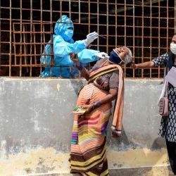 Una mujer reacciona cuando una trabajadora de salud le toma una muestra de hisopo para realizar una prueba del coronavirus Covid-19 antes de ir a un campamento médico para víctimas de inundaciones en un barrio pobre después de las fuertes lluvias en Hyderabad. | Foto:Noah Seelam / AFP