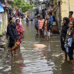 Los residentes se reúnen en una calle inundada frente a sus casas luego de las fuertes lluvias en Hyderabad. | Foto:Noah Seelam / AFP