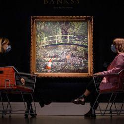 Los asistentes posan junto a una obra de arte titulada Muéstrame el Monet del artista callejero británico Banksy durante una sesión fotográfica para la subasta de arte contemporáneo principal en Sotheby's Galleries en el centro de Londres. | Foto:Tolga Akmen / AFP