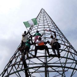 Los manifestantes suben a un mástil de telecomunicaciones mientras llevan la bandera nacional de Nigeria durante una manifestación para presionar por el desguace del Escuadrón Especial Ant-Robbery (SARS) en la autopista Abuja-Keffi Expressway, Abuja, Nigeria. | Foto:Kola Sulaimon / AFP