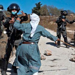 Un palestino se enfrenta a miembros de las fuerzas de seguridad israelíes después de que intervinieron en las riñas entre colonos judíos y agricultores palestinos que intentaban acceder a sus tierras para cosechar aceitunas, en la aldea de Burqah, en Cisjordania. | Foto:Abbas Momani / AFP