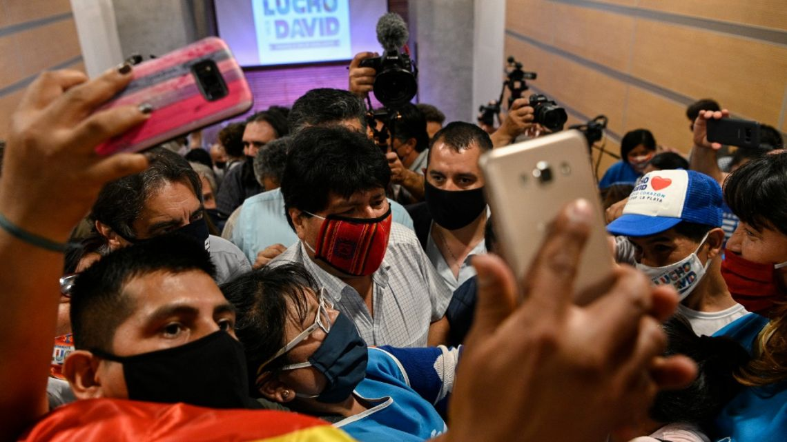 Bolivian ex-president Evo Morales (centre) is surrounded by supporters after offering a press conference in Buenos Aires on October 19, 2020.