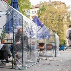 Los invitados se sientan en un pequeño invernadero como medida de protección contra el coronavirus (COVID-19) en una cafetería en Berlín.   Foto:Stefanie Loos / AFP
