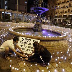 Activistas israelíes antigubernamentales colocan velas en honor a las víctimas de la pandemia de coronavirus y para protestar contra el gobierno, en el centro de Jerusalén.   Foto:MENAHEM KAHANA / AFP