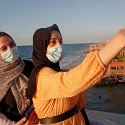 Mujeres palestinas se toman una selfie al atardecer en la ciudad de Gaza en medio de estrictas restricciones debido a la pandemia de COVID-19.   Foto:Mohammed Abed / AFP