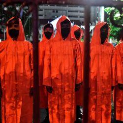 La policía usa impermeables para protegerse de la lluvia mientras montan guardia en la sede de la policía en Bangkok, mientras los manifestantes a favor de la democracia se reunieron frente a las instalaciones para oponerse al arresto de los manifestantes en una manifestación improvisada anterior en el Monumento a la Democracia.   Foto:Lillian Suwanrumpha / AFP