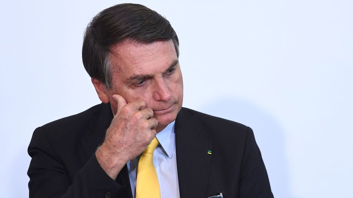 Brazilian President Jair Bolsonaro gestures during an event to announce the clinical study of the use of Nitazoxanide in an early treatment against Covid-19, at Planalto Palace in Brasilia, on October 19, 2020.