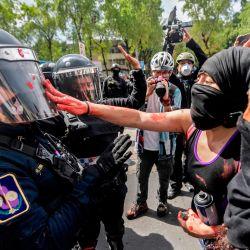 Un manifestante pinta el casco de una policía antidisturbios cerca de una estatua de Cristóbal Colón que estaba rodeada por una valla metálica de protección, durante el Día de la Raza en la Ciudad de México. | Foto:Pedro Pardo / AFP