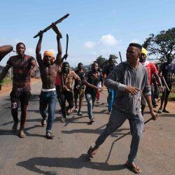 Gesto de jóvenes nigerianos mientras persiguen a un grupo contrario durante los enfrentamientos entre jóvenes en Apo, Abuja, Nigeria, luego de las manifestaciones en curso contra la brutalidad injusta de la Unidad de la Fuerza de Policía de Nigeria, el Escuadrón Especial Anti-Robo (SARS). | Foto:Kola Sulaimon / AFP