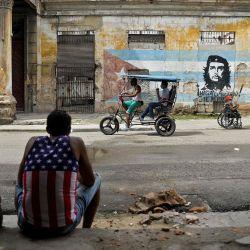Un hombre vestido con una camiseta sin mangas con un diseño de la bandera de Estados Unidos descansa en La Habana, en medio de la pandemia del nuevo coronavirus COVID-19. | Foto:Yamil Lage / AFP