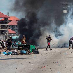 Los manifestantes gesticulan y arrojan piedras frente a una nube de gas lacrimógeno, durante una protesta masiva la mañana después de que se publicaran los resultados preliminares para cinco comunas en Conakry. | Foto:John Wessels / AFP