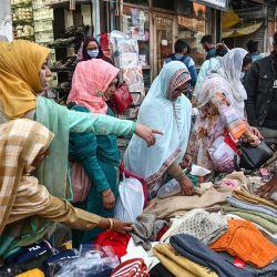 Las mujeres compran ropa y otros productos en un mercado en Srinagar. | Foto:Money Sharma / AFP