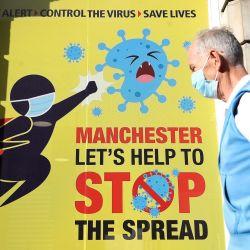 Inglaterra, Manchester: una persona que lleva una máscara facial pasa junto a un cartel de coronavirus (COVID-19) en Deansgate mientras el gobierno se prepara para imponer nuevos controles estrictos del coronavirus a 2,8 millones de personas después de que las conversaciones con los líderes locales del Gran Manchester no lograran llegar a un acuerdo. | Foto:Martin Rickett / PA Wire / DPA