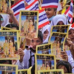 Los estudiantes sostienen fotografías del rey Maha Vajiralongkorn y la reina Suthida de Tailandia mientras ondean la bandera nacional tailandesa mientras participan en una manifestación para mostrar su apoyo al establecimiento real tailandés en el distrito de Muang Pattani en la provincia sureña de Pattani, Tailandia. | Foto:Tuwaedaniya Meringing / AFP