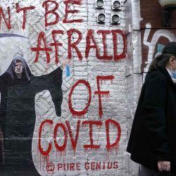 Una persona pasa junto a un mural del artista que se conoce con el nombre de  | Foto:TIMOTHY A. CLARY / AFP