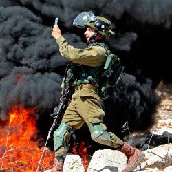 Un miembro de las fuerzas de seguridad israelíes toma una fotografía con su teléfono durante los enfrentamientos con manifestantes palestinos después de una manifestación semanal en la aldea de Kfar Qaddum, en Cisjordania. | Foto:Jaafar Ashtiyeh / AFP