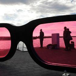 La gente de pie detrás de grandes lentes rosas observa el mar durante un día soleado. | Foto:Bernd Wüstneck / DPA