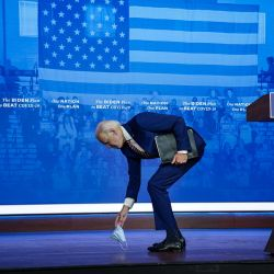 El candidato presidencial demócrata Joe Biden recoge su mascarilla protectora después de dejarla caer mientras abandonaba el escenario luego de sus comentarios para combatir la pandemia de coronavirus en el teatro The Queen el en Wilmington, Delaware. | Foto:Drew Angerer / Getty Images / AFP