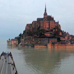 La fotografía aérea muestra una carretera parcialmente cubierta de agua desde donde la gente mira el Mont-Saint-Michel, en Normandía, noroeste de Francia, rodeada por el mar durante la marea alta. - Desde 1979, el sitio del Mont Saint-Michel y su bahía es un sitio del patrimonio mundial de la UNESCO. | Foto:Damien Meyer / AFP