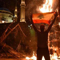 Un hombre libanés iza una bandera nacional mientras el 'puño de la Revolución', símbolo del levantamiento libanés de octubre de 2019, arde después de ser incendiado durante los enfrentamientos entre manifestantes antigubernamentales y partidarios del ex primer ministro Saad Hariri, en la plaza de los Mártires, en la capital, Beirut. | Foto:AFP