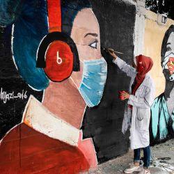 Artistas palestinos pintan murales de colegialas vestidas con máscaras en la ciudad de Gaza, en medio de la nueva crisis pandémica del coronavirus. | Foto:Mohammed Abed / AFP