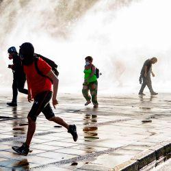 Los manifestantes huyen de un spray de la policía antidisturbios durante una protesta contra el gobierno del presidente chileno Sebastián Piñera en Santiago, antes del referéndum. | Foto:Martin Bernetti / AFP
