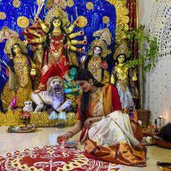 Esta foto muestra al maquillador y modelo Thakkar Virali, posando frente a un ídolo de arcilla de la diosa hindú Durga de diez manos durante las celebraciones del festival 'Durga Puja' en Ahmedabad. | Foto:SAM PANTHAKY / AFP