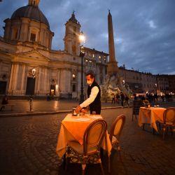 Un empleado limpia una mesa en una terraza vacía en la plaza Piazza Navona en Roma, antes de que entre en vigor un toque de queda por el virus nocturno en la región de Lazio como medida contra la propagación de la pandemia Covid-19. | Foto:Filippo Monteforte / AFP