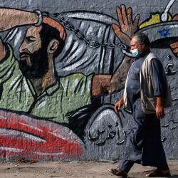 Un hombre palestino que lleva una máscara protectora pasa junto a un mural en el campo de refugiados de Nusseirat, en el centro de la Franja de Gaza, y expresa su apoyo al detenido administrativo bajo custodia israelí Maher al-Akhras, cuya salud se ha deteriorado mientras está en huelga de hambre durante casi 85 días. | Foto:Mohammed Abed / AFP