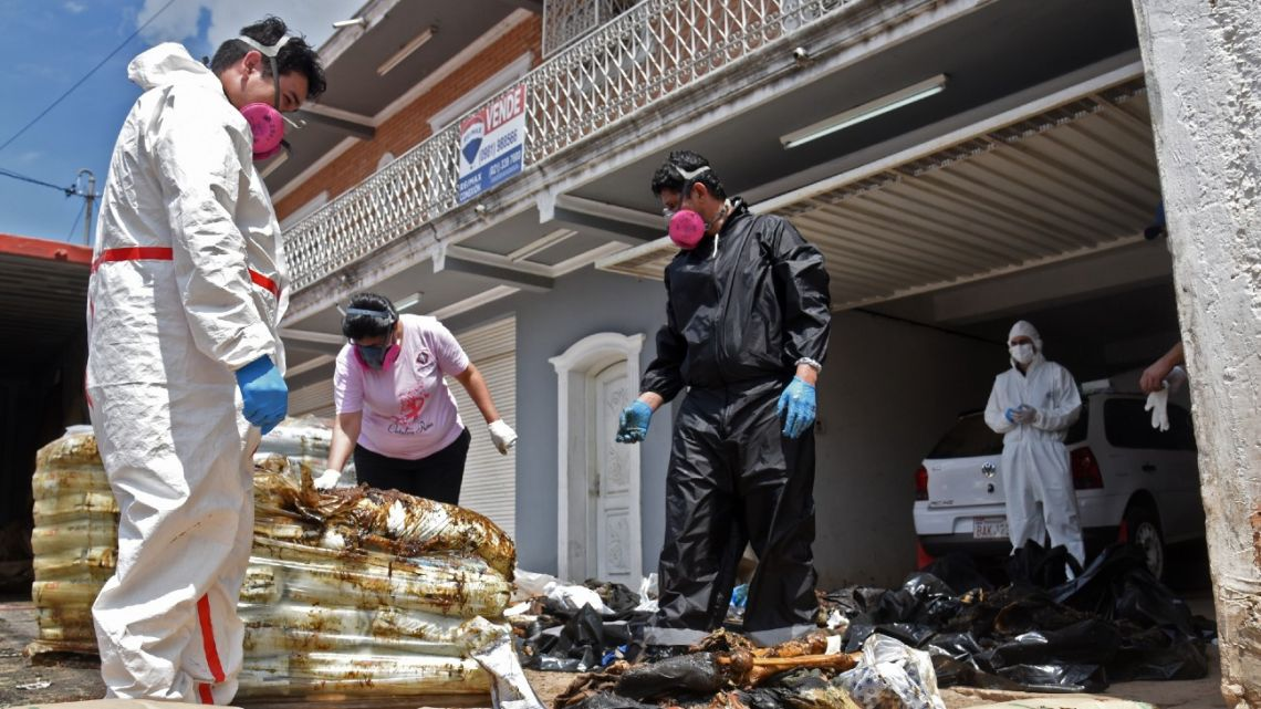 Forensic experts inspect parts of decomposed bodies found inside a container coming from Serbia, in Asunción, on October 23, 2020.