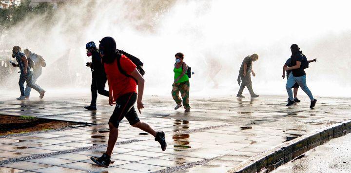 Los manifestantes huyen de un spray de la policía antidisturbios durante una protesta contra el gobierno del presidente chileno Sebastián Piñera en Santiago, antes del referéndum.