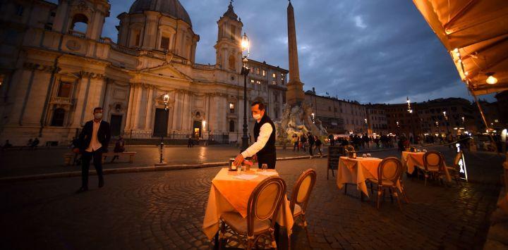 Un empleado limpia una mesa en una terraza vacía en la plaza Piazza Navona en Roma, antes de que entre en vigor un toque de queda por el virus nocturno en la región de Lazio como medida contra la propagación de la pandemia Covid-19.
