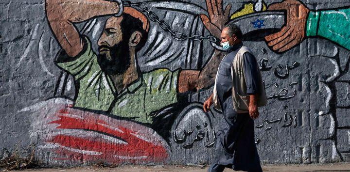 Un hombre palestino que lleva una máscara protectora pasa junto a un mural en el campo de refugiados de Nusseirat, en el centro de la Franja de Gaza, y expresa su apoyo al detenido administrativo bajo custodia israelí Maher al-Akhras, cuya salud se ha deteriorado mientras está en huelga de hambre durante casi 85 días.