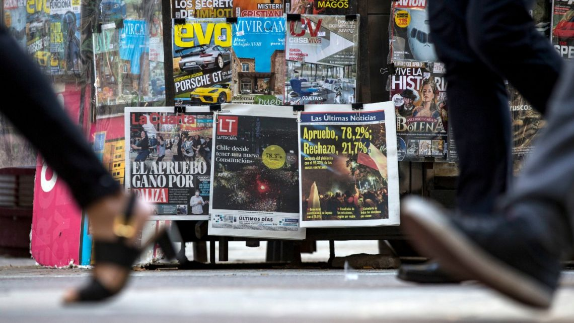 People walk past a kiosk displaying the covers of Chilean newspapers the day after a referendum in Santiago on October 26, 2020.