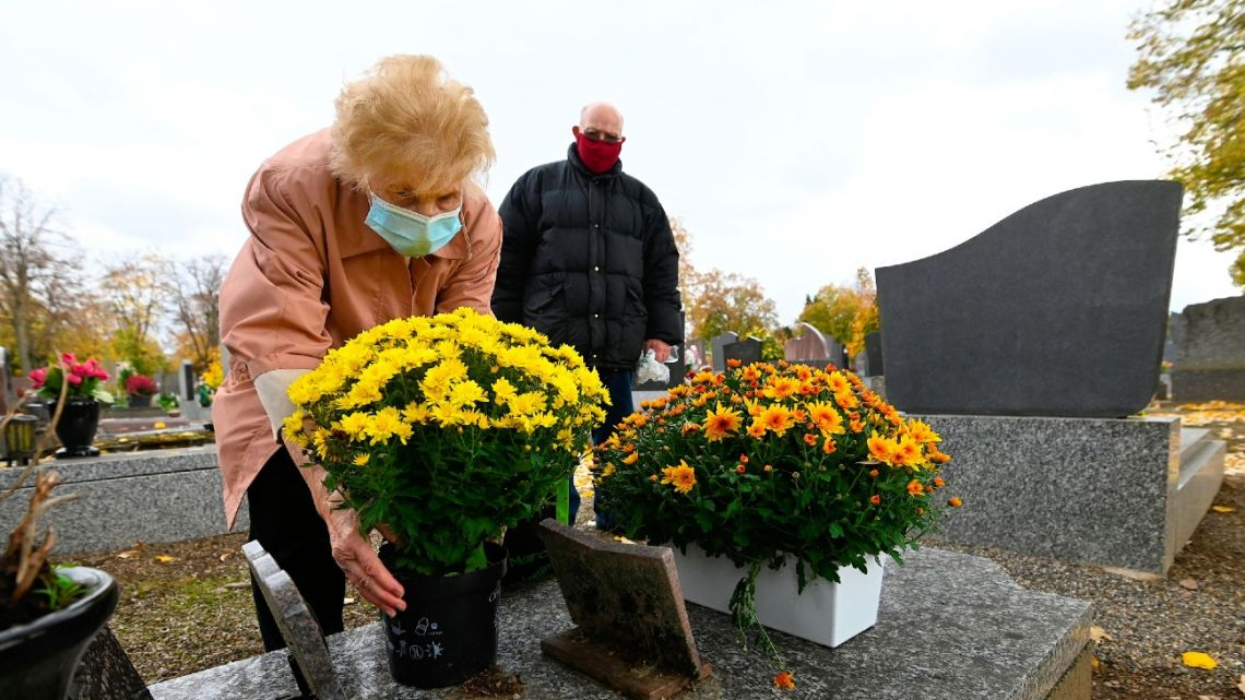 A woman lays flowers on a grave at the cemetery, in Mulhouse, eastern France, on October 29, 2020 as part of the All Saint's festivities, on the eve of the implementation of a general lockdown in France to curb the spread of the Covid-19's second wave (novel coronavirus).
