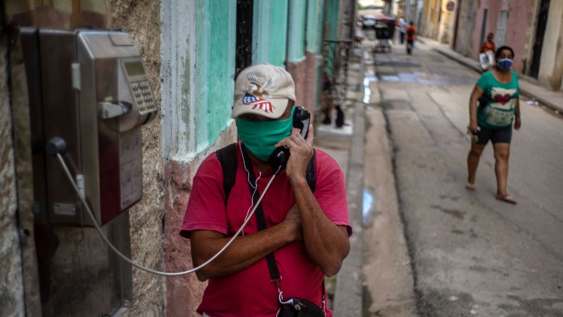 Wearing a protective face mask amid the new coronavirus pandemic, a man speaks on a public phone in Old Havana, Cuba, Monday, October 26, 2020.