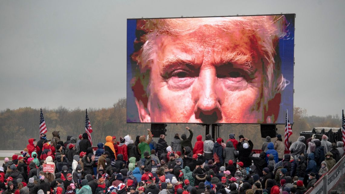 Supporters of US President Donald Trump watch a video screen showing his face during a campaign event on Tuesday, October 27, 2020, in Lansing, Michigan.