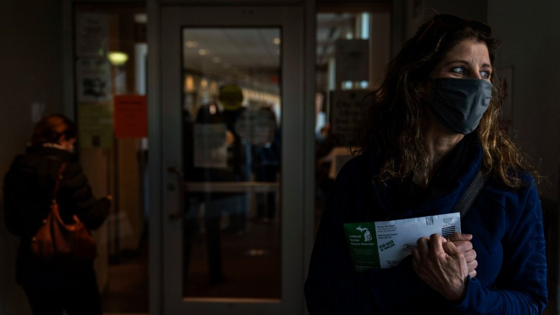 Diane Spiteri clutches her absentee ballot before dropping it off at the city clerk's office in Warren, Michigan, Wed, October 28, 2020.