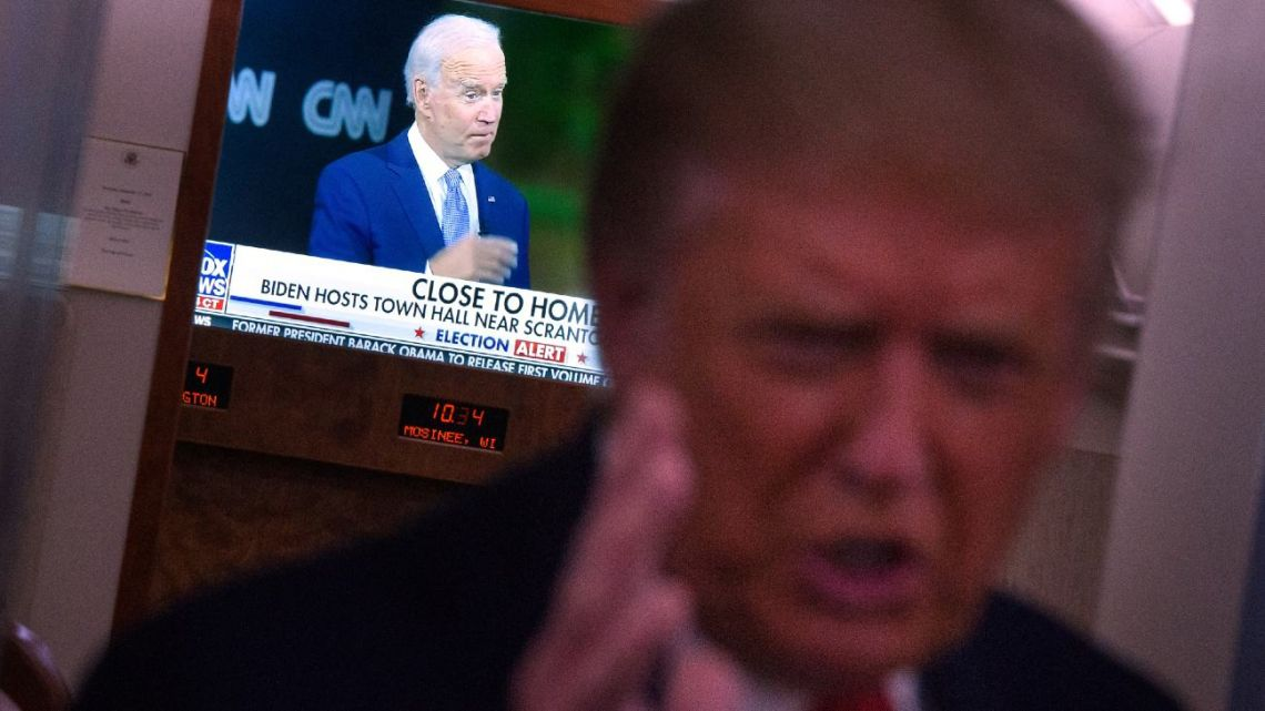 An image of Democratic presidential candidate Joe Biden is seen on a TV as US President Donald Trump speaks to reporters onboard Air Force One after a campaign rally in Mosinee, Wisconsin on September 17, 2020.