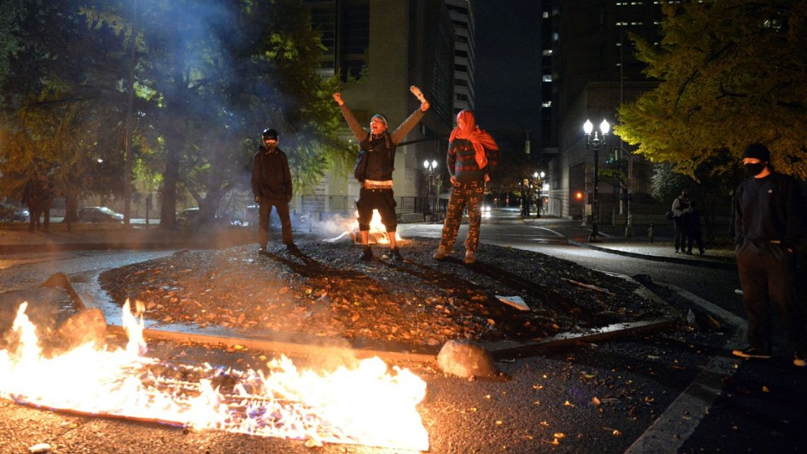 Protesters burn the American flag outside the Mark O. Hatfield United States Courthouse in Portland, Oregon, on November 4, 2020.